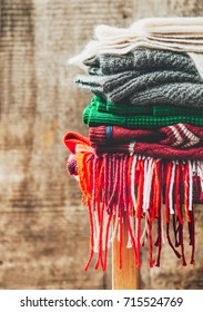 A stack of warm winter clothes and sweaters of wool on a wooden background.