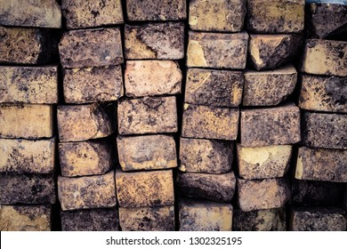 A stack of weathered bricks with dried mud and grass provides a grungy background.