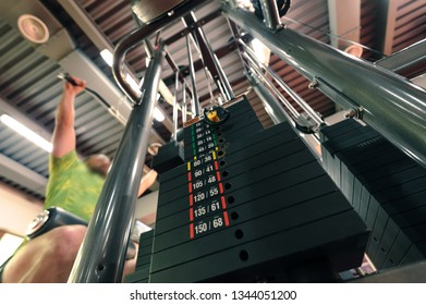 Stack of weights in complex gym machine, motion blurred unrecognizable person doing upper traction with a wide grip at background, perspective closeup, selective focus