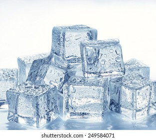 stack of wet ice cubes on blue background