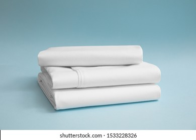 Stack of white bedding against blue backdrop, folded soft bed clothes, stack of white cotton sheets on a blue background for advertising, commercial and mock up