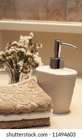 Stack of white and brown towels and bottle of liquid soap with some dry flowers in the bathroom