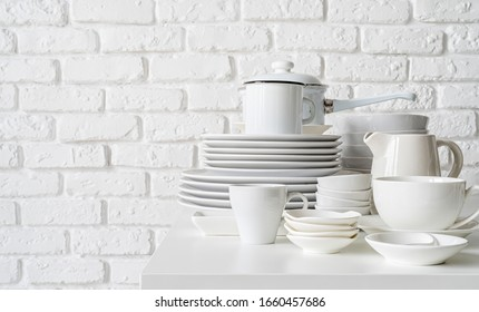 stack of white ceramic dishes and tableware on the table on white brick wall background with copy space