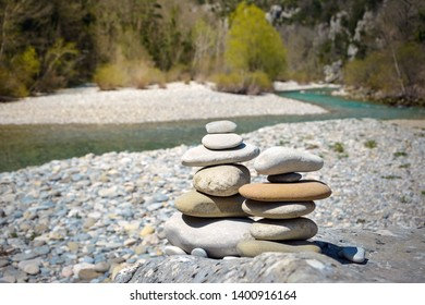 Stack of white pebbles stone against blue mountain stream background for spa, balance, meditation and zen theme