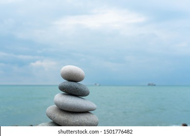 Stack of white pebbles stone against blue sea background for spa, balance, meditation and zen theme. Beautiful background