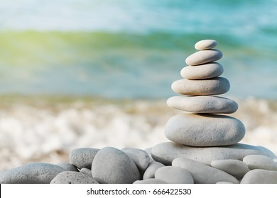 Stack of white pebbles stone against blue sea background for spa, balance, meditation and zen theme.