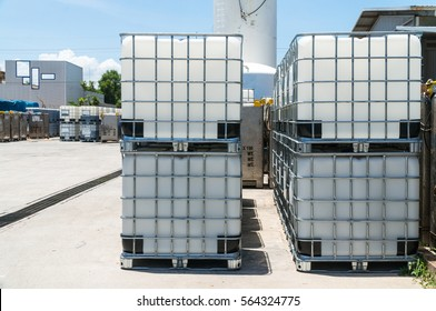 Stack of white plastic IBC Tank for liquid chemical storage.