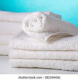 stack of white spa towels on blue background