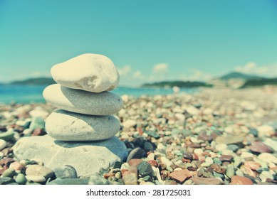 Stack of white stones balancing on the pebbly beach, on a sunny day. Image filtered in faded, washed out, retro style; summer vintage concept. Concept of harmony, well-being, wellness and zen.