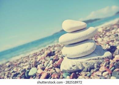 Stack of white stones balancing on the pebbly beach. Image filtered in faded, washed out, retro style; summer vintage concept. Concept of harmony, well-being, wellness and zen. Tilted perspective.