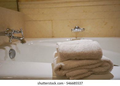 stack of white towel on bathtab in bathroom