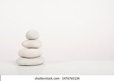 Stack of  white zen stones on a white background with copy space