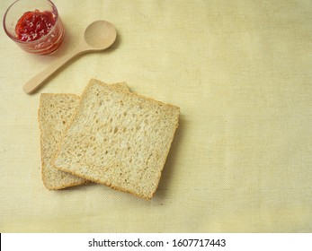 Stack whole wheat bread or sandwich wheat loaf and wood spoon on sackcloth background, top view picture.