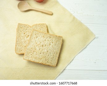 Stack whole wheat bread or sandwich wheat loaf and wood spoon on sackcloth and white wooden background. top view picture.