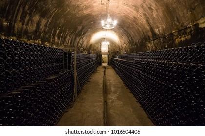 Stack of wine bottles in an old dark wine cellar. Champagne bottles. Abrau-Durso, Russia