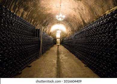 Stack of wine bottles in an old dark wine cellar. Champagne bottles. Abrau-Durso, Russia