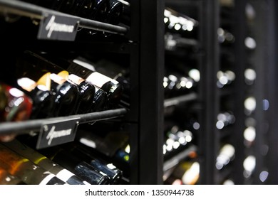 Stack of wine bottles in an old dark wine cellar. Champagne bottles. Spirits & liquor store