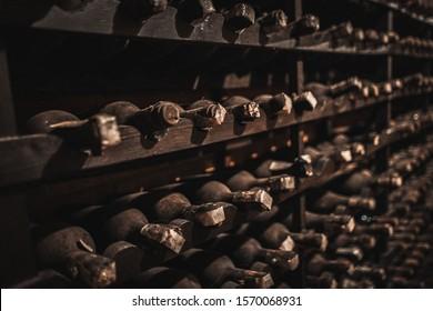 Stack of wine bottles in an old dark wine cellar.