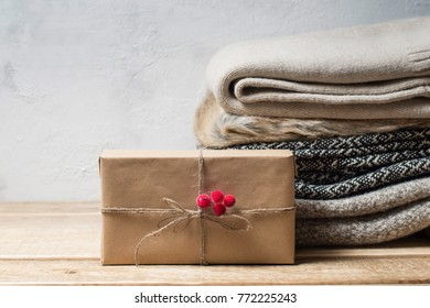 Stack of winter clothes and gift over grey. monochrom. copy-space