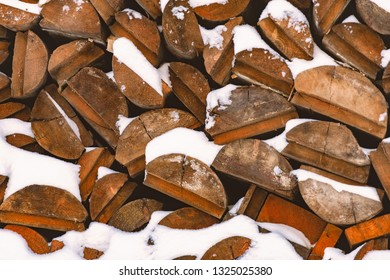 Stack of wood logs. Preparation of firewood for the winter. Pile of chopped lumber covered with snow.