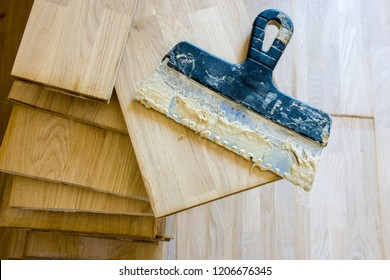 Stack of wood parquet or floorboard as floor covering with spatula on it with parquet adhesive glue on it top view. Preparation for installation of parquet on floor by masters or workers