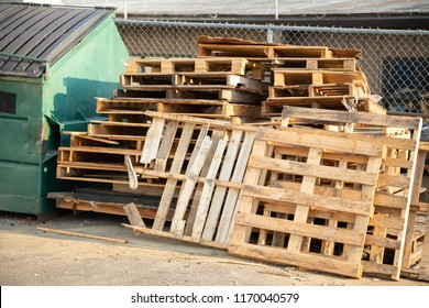 Stack of wood shipping pallets with beside a garbage dumpster