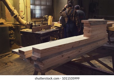 Stack of wooden blanks at the sawmill. Workers on background.