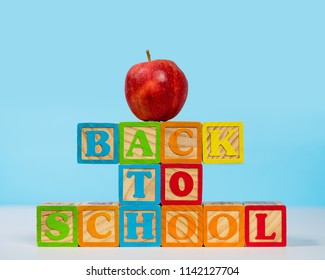 Stack of wooden blocks stacked to spell Back to School with red apple on top against blue background