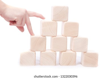 Stack wooden cubes.Hand establishes block tower isolated.