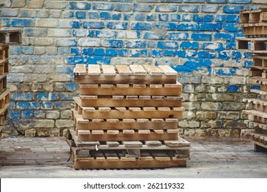 A stack of wooden pallets on the background of wooden wall