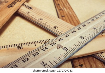stack of wooden rulers on a tan table, rulers vary in color