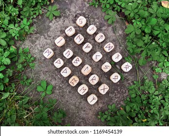 A stack of wooden runes at forest. Wooden runes lie on a rock background in the green grass. Runes are cut from wooden blocks. On each rune symbol for fortune telling is designated.