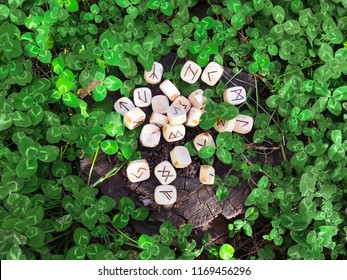 A stack of wooden runes at forest. Wooden runes lie on a wood background in the green clover grass. Runes are cut from wooden blocks. On each rune symbol for fortune telling is designated.