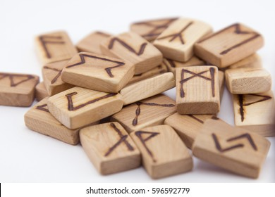 A stack of wooden runes. Wooden runes lie on a table on a white background. Runes are cut from wooden blocks. On each rune symbol for fortune telling is designated. Ukraine. Kiev. 03/04/2017