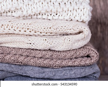 A stack of woolen sweater, plaid. Warm clothing. Home atmosphere, winter clothing. Gray, white and brown sweater. Warm and cozy. Knitted clothes. Cozy atmosphere.