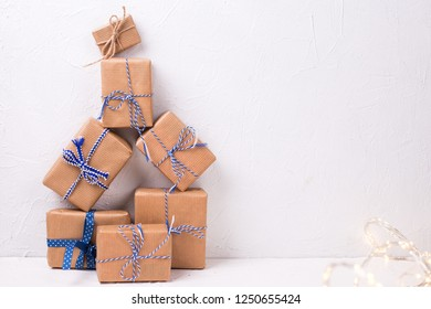 Stack of wrapped boxes with presents  and fairy lights on white textured background. Selective focus. Place for text. Winter holiday, Christmas, New Year.