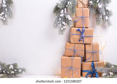 Stack of wrapped boxes with presents, fir tree branches and fairy lights on white textured background. Selective focus. Winter holiday, Christmas, New Year. Place for text.