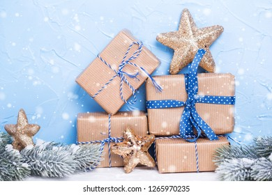 Stack of wrapped boxes with presents, fir tree branches  and golden stars on  blue textured background. Selective focus. Place for text. Winter holiday, Christmas, New Year.