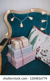 Stack of wrapped christmas gifts on vintage chair and christmas lights on background.