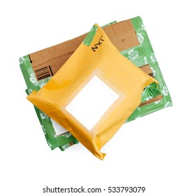 A stack of wrapped up parcels on a white background, from above, with blank labels and green recycled parcel tape