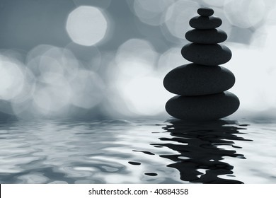 Stack of zen pebbles in the moonlight with defocused background highlights
