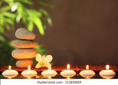 Stack of zen stones and aromatic candles on table,Zen concept.