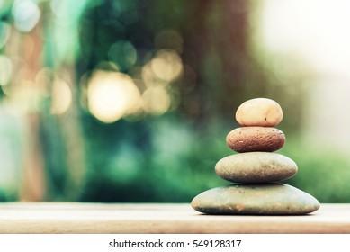 Zen-Stein auf dem Boden mit unscharfem Naturhintergrund.