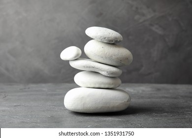 Stack of zen stones on table against grey background