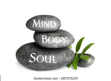 Stack of zen stones with words Mind, Body, Soul on white background