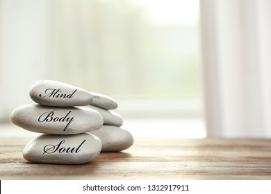 Stack of zen stones with words Mind, Body, Soul on table in room