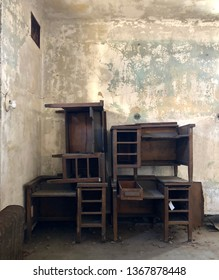 Stacked and abandoned antique wooden furniture desks piled in abandoned empty room