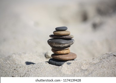 Stacked Beach Stones Closeup with sand behind