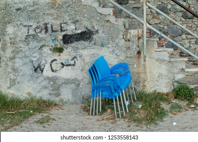 Stacked blue chairs, they are tied with chain and padlock to the railing of a staircase, on the wall it was written with paint, toilet and wc