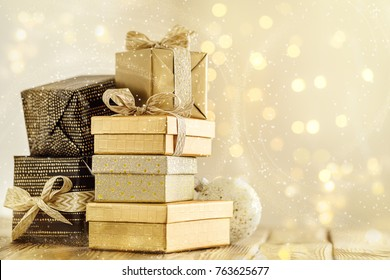 Stacked boxes wrapped in gold ribbons in magical sparkling snow.